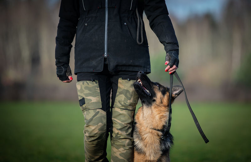 Midsection of man with dog standing outdoors