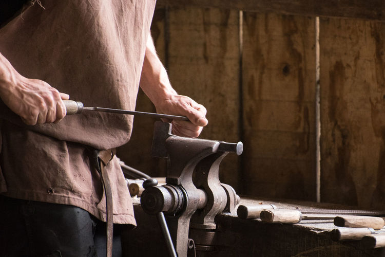 Midsection of man working in workshop