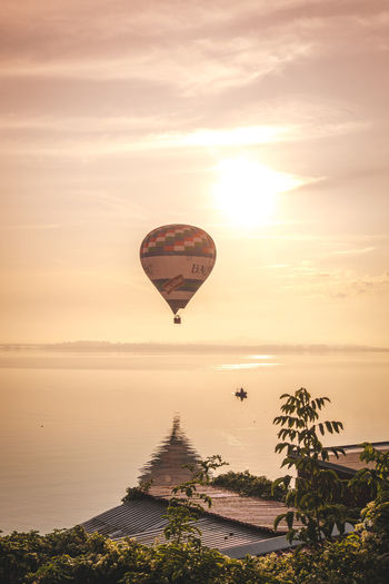 Hot air balloon flying over sea against sky during sunset