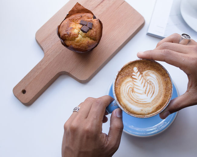 Cappuccino Close-up Coffee - Drink Coffee Cup Cutting Board Day Drink Food Food And Drink Freshness Froth Art Frothy Drink Holding Human Body Part Human Hand Indoors  Morning Muffin One Person Ready-to-eat Real People Refreshment Table White Background