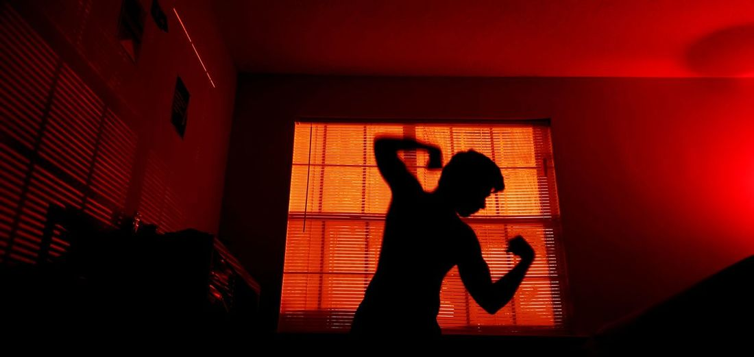 Silhouette woman standing against wall at home