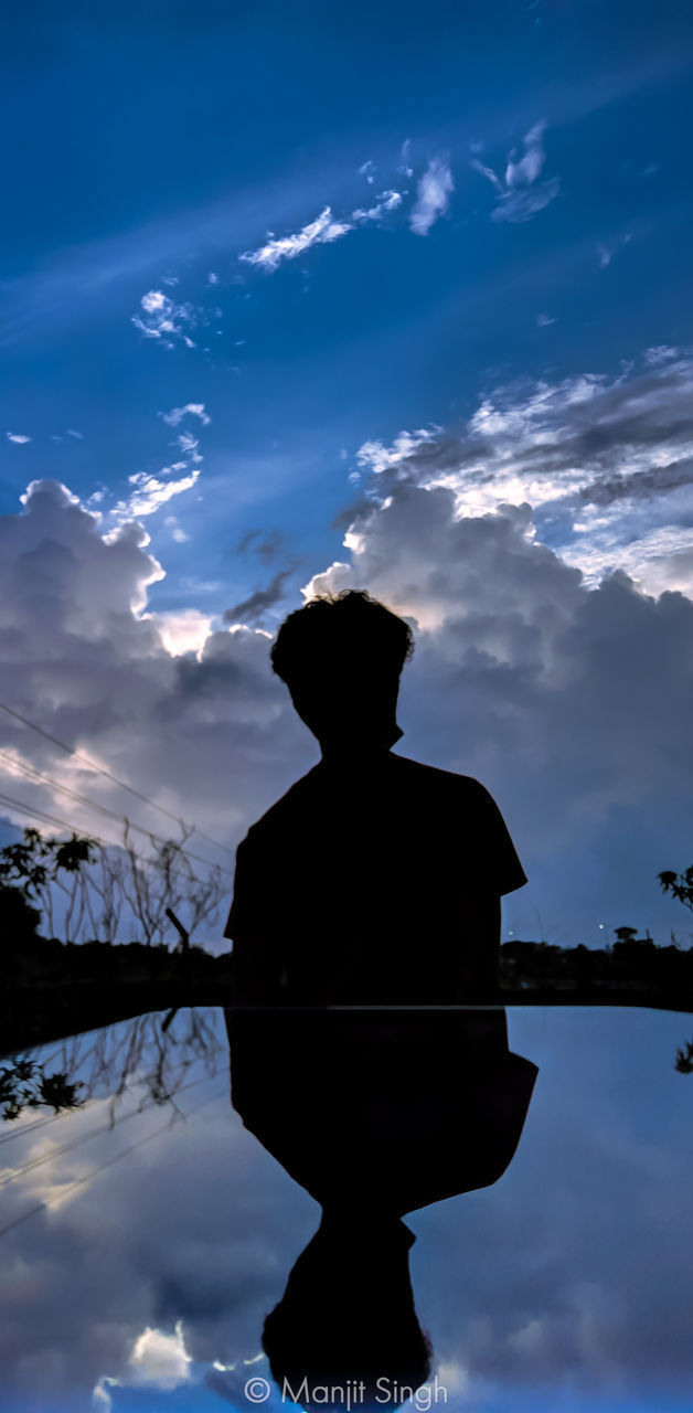 REAR VIEW OF SILHOUETTE MAN STANDING AGAINST SKY
