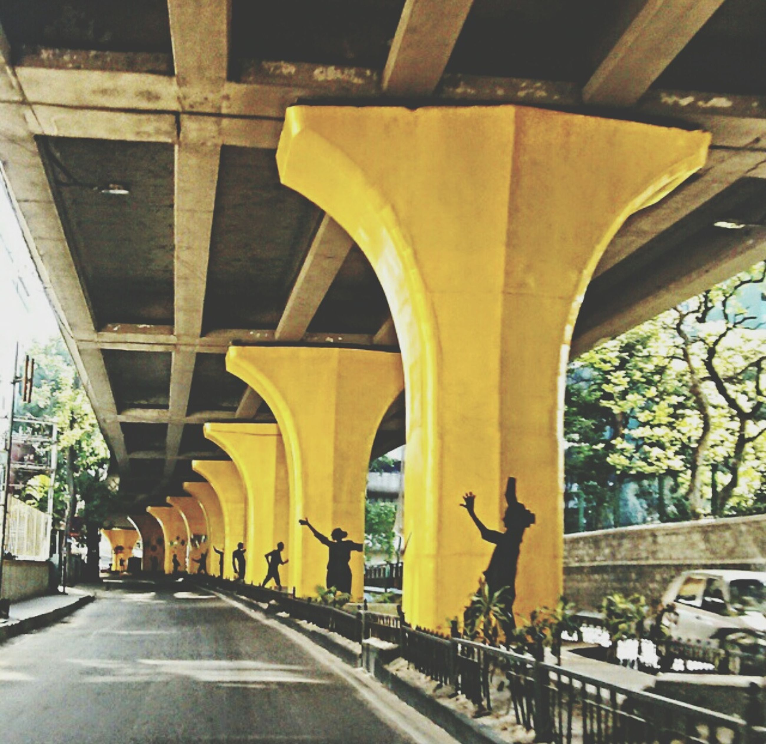architecture, built structure, transportation, arch, the way forward, building exterior, architectural column, diminishing perspective, road, city, bridge - man made structure, connection, street, incidental people, in a row, car, ceiling, tree, no people, illuminated