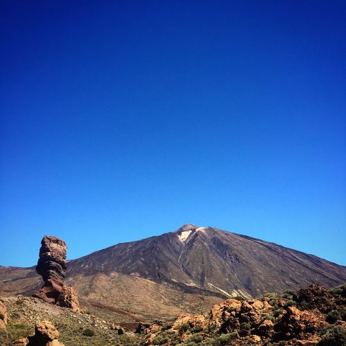 View of volcanic landscape against blue sky