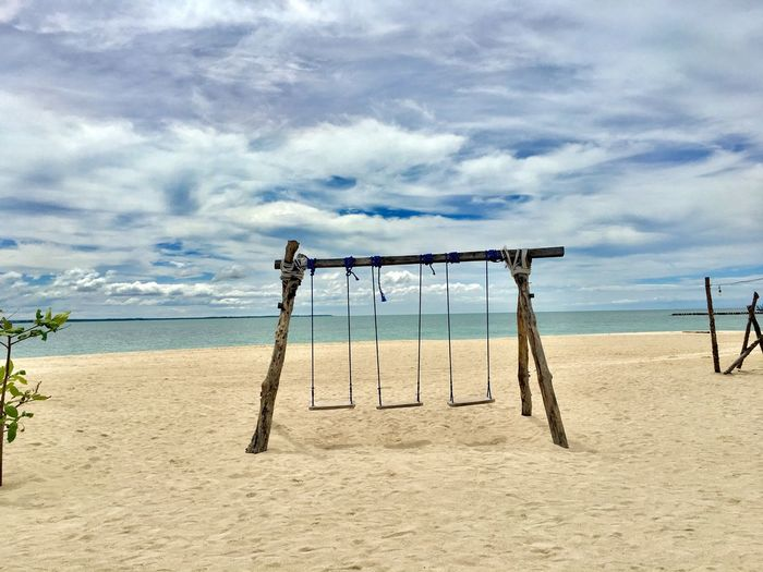 View of swing at shore of beach