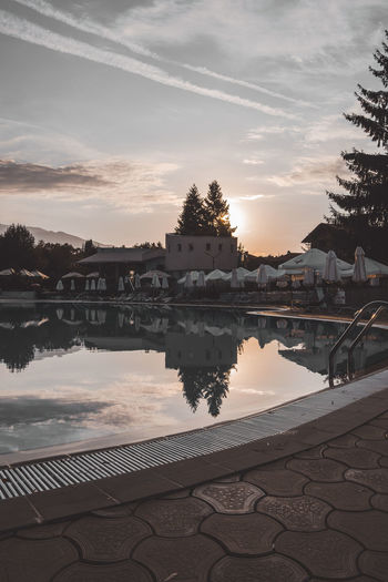 Swimming pool by lake against sky during sunset
