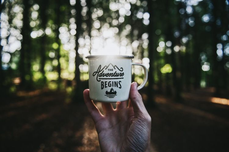 """An enamel mug with the quote """"Let the adventure begin"""" in the forrest."""