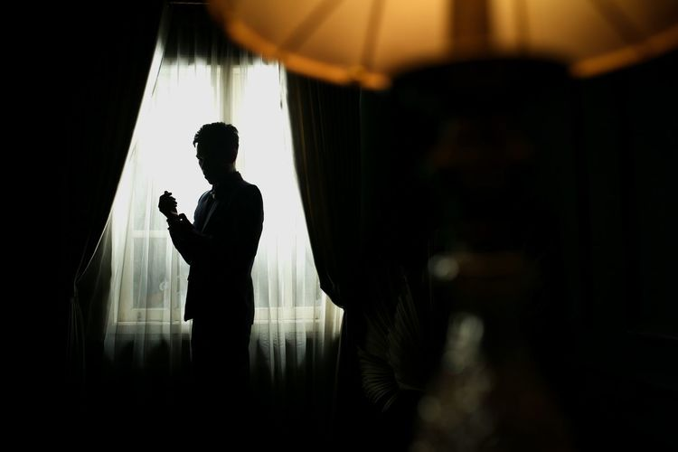 Side view of silhouette man using mobile phone