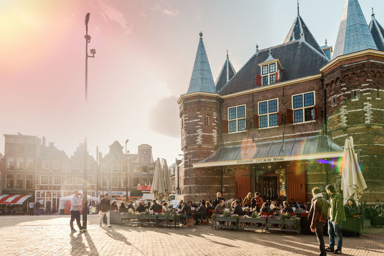 Sunset in the City Building Exterior Architecture Built Structure City Group Of People Crowd Building Large Group Of People Real People Adult Street Sky Lifestyles Sunlight City Life Outdoors Amsterdam