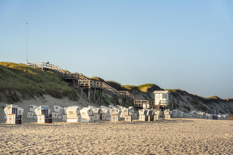 Hooded chair on beach against sky