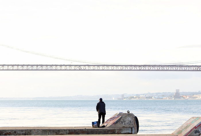 One Person One Man Only Rear View Water People Bridge - Man Made Structure Sky Day Sea Horizon Over Water Full Length Outdoors Architecture River Fisherman Fishing Tejo River Portugal 25 De Abril Bridge Adapted To The City Uniqueness