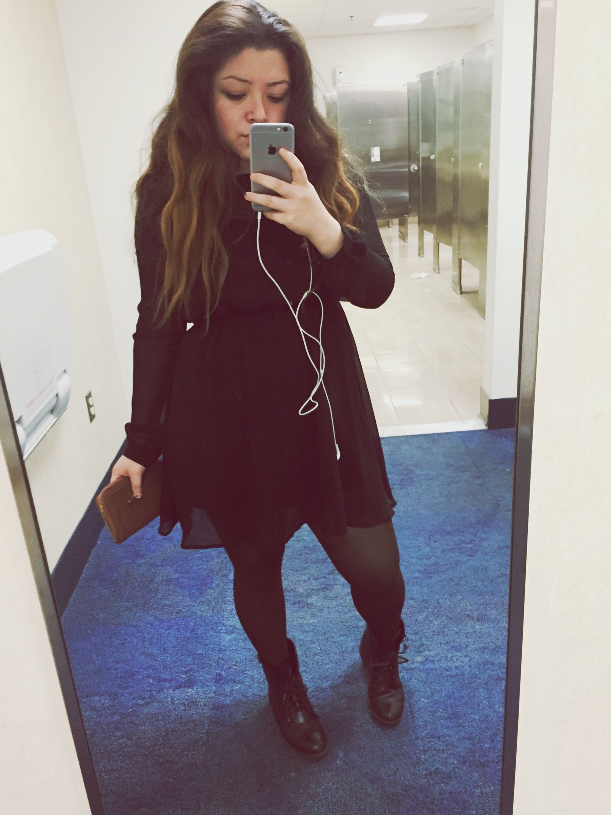 young adult, indoors, lifestyles, young women, leisure activity, person, casual clothing, front view, standing, full length, home interior, technology, three quarter length, wireless technology, mirror, fashion, long hair