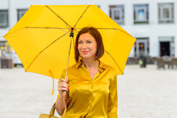 Woman holding umbrella while standing on road against buildings