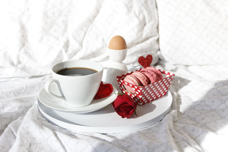 Close-up of coffee cup and breakfast on bed
