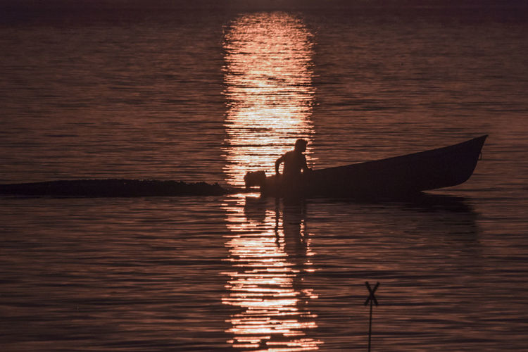Silhouette man sailing on motorboat in river during sunset