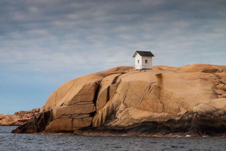 Hut On Rock Formation At Sea Shore Against Sky