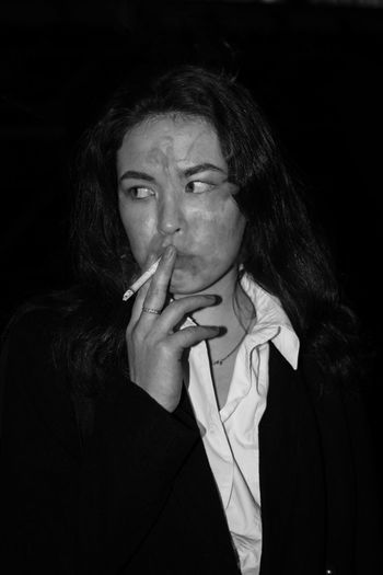 Portrait of young woman smoking cigarette against black background
