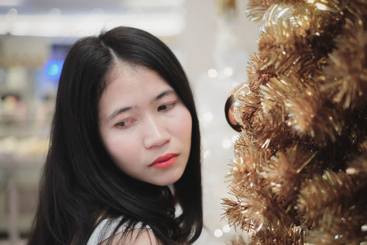 Close-up portrait of young woman with christmas tree
