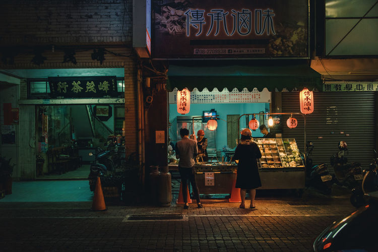 Food vendors in Tainan Architecture Building Exterior Built Structure City Dramatic Full Length Illuminated Lifestyles Men MOVIE Night Old People Real People Snack Standing Store Story Women