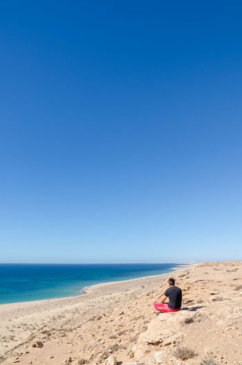 Rear View Of Man Sitting On Beach Against Clear Blue Sky
