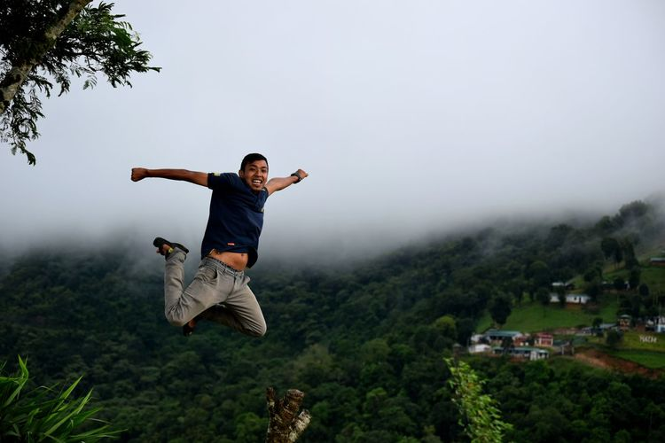 Man jumping in mid-air against mountains during foggy weather