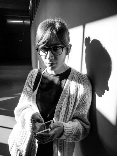 Blackandwhite Casual Clothing Focus On Foreground Front View Indoors  Leisure Activity Lifestyles Light And Shadow Person Portrait Portrait Of A Woman Shadow Smartphone Team Awesome Technology Technology I Can't Live Without Young Adult Young Women Wearing Glasses Indoors  Close-up Eyeem Office