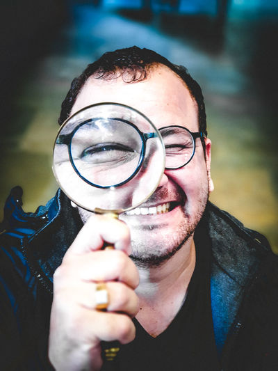 Portrait of young man holding magnifying glass