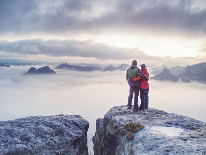 Happy couple with enjoy view after climbing top of rocky mountain. partners watch beauty wild nature