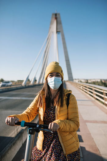 Woman standing on bridge against clear sky
