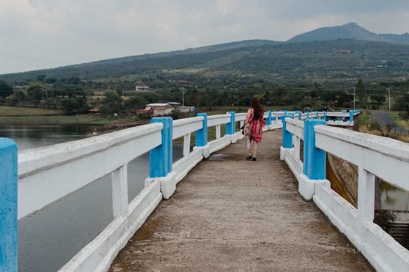 Woman standing on footbridge against mountains