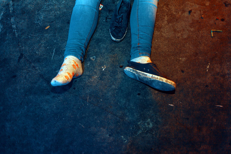 The detail on the shoes and feet of a collapsed girl after a party