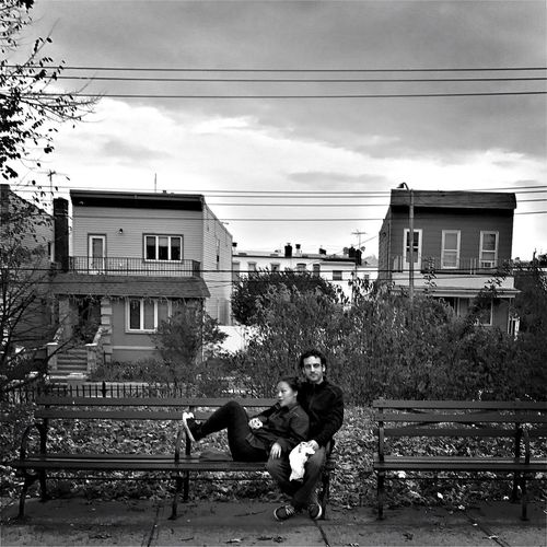 Man sitting on sidewalk in city against sky