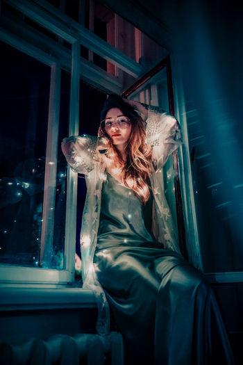 Portrait Of Woman With Illuminated String Light Sitting On Window Sill