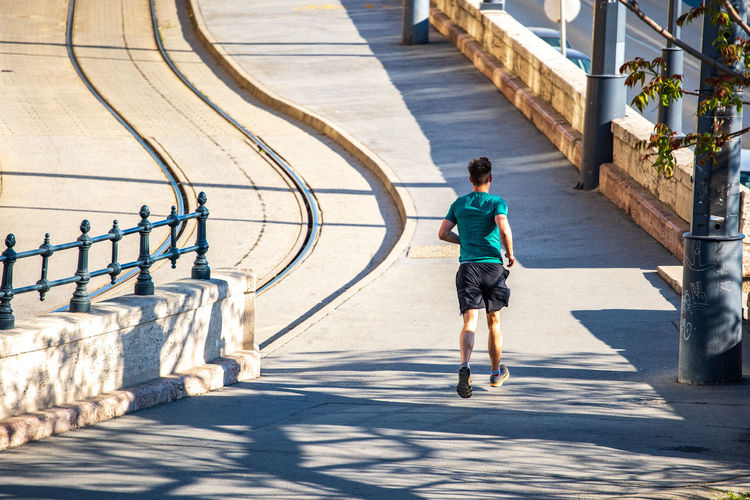 Rear view of man running on footpath in city