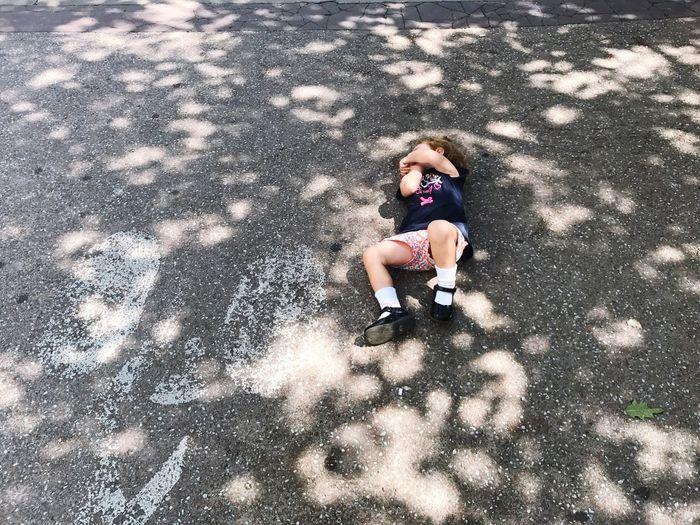 High angle view of girl lying on footpath