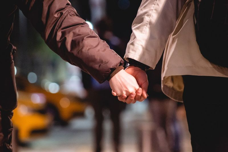 Midsection of couple holding hands in city