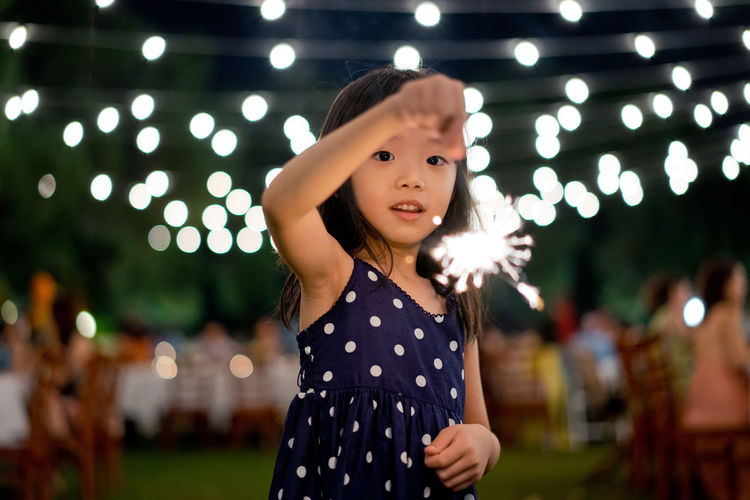 Portrait Of Girl Holding Sparkler While Standing Against Lights During Night