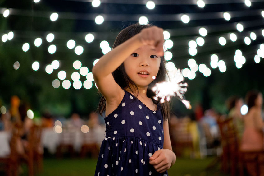 Little girl plays with sparkler light stick in Christmas environment One Person Illuminated Focus On Foreground Child Real People Polka Dot Childhood Leisure Activity Night Girls Portrait Standing Women Front View Spotted Lifestyles Looking At Camera Cute Innocence Hair Hairstyle Outdoors Sparkler Christmas Celebration Event