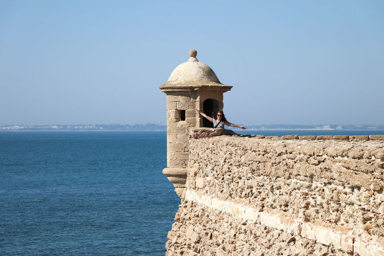 Woman posing at a small tower at a castle near the sea Architecture Water Built Structure Sea Sky Building Exterior Day Horizon Over Water Clear Sky Nature Horizon History Vertebrate Scenics - Nature Tower Wall The Past No People Copy Space Stone Wall