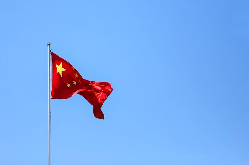 Low angle view of chinese flag against clear blue sky