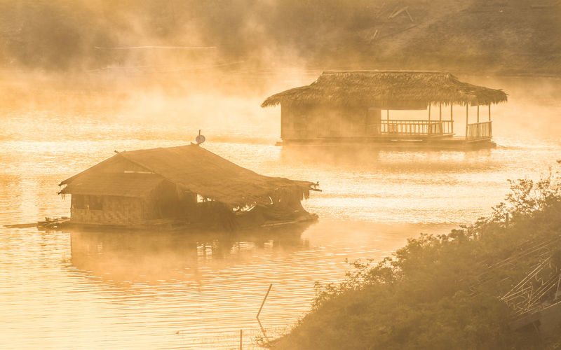 Huts in river at sangkhla buri district during foggy weather