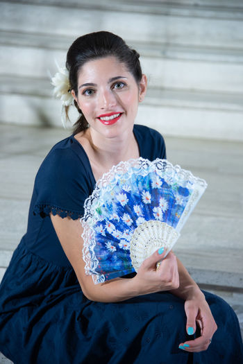 Portrait Of Young Female Model Holding Hand Fan While Sitting On Steps