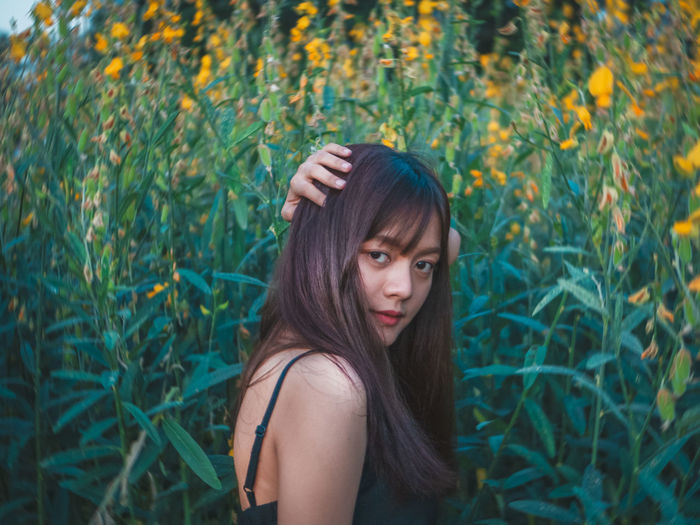 Portrait of beautiful young woman standing amidst plants