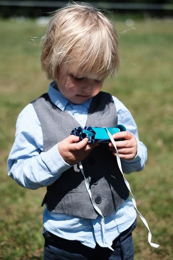 Childhood Boys One Person Holding Leisure Activity Real People Casual Clothing Outdoors Day Concentration Technology Front View Lifestyles Standing Playing Nature Grass Camera - Photographic Equipment Photography Themes One Boy Only