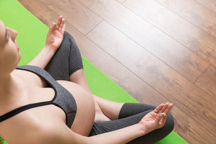 Low section of woman sitting on hardwood floor