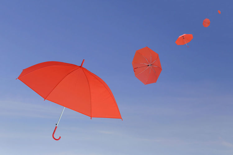 Red umbrella blown by the wind in concept for management business idea on blue sky background. Blue Sky White Clouds Business Concepts Leadership Is Powerful Management Potential Red Umbrella Blue Sky Blue Sky And Clouds Blue Sky And White Clouds Blue Sky With Clouds Business Finance And Industry Businessman Concept Conceptual Idea Ideal Ideas Leadership Leadership Conference Leadership Redefined Management Management; Red Umbrellas Sun Protection Wind