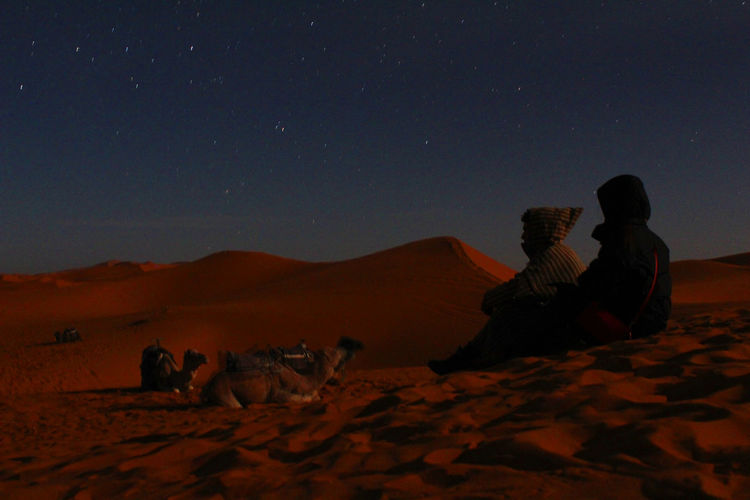 Rear view of man sitting on desert against sky at night