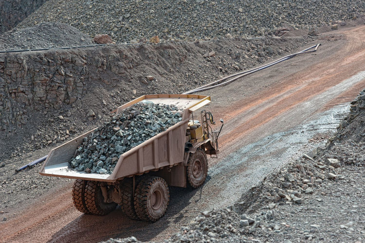 dumper truck with loaded stones driving along in a quary. mining industry. Production Dust Driving Transportation Construction Materials Construction Material Rocks Loading Steinbrecher Dumper Truck Dumper Steinbruch Stone Pit Stonepit Quarry Rock Quarry Mine Mining Minerals