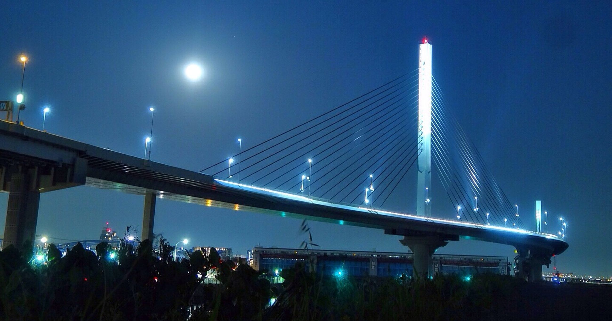 illuminated, night, low angle view, architecture, built structure, connection, sky, bridge - man made structure, lighting equipment, blue, engineering, street light, modern, light - natural phenomenon, city, railing, transportation, moon, no people, outdoors
