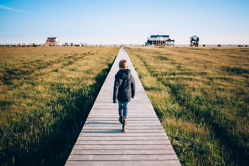 Rear view of boy walking on boardwalk over grassy field